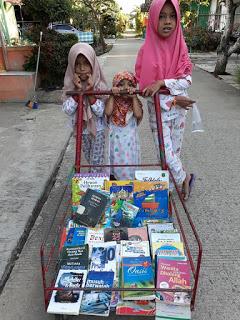Bilqis, Yasmin dan Asifa, putri dari ibu Kurnia saat ikut membantu ibunya keliling kompleks menawarkan buku  untuk dibaca warga. (Ist)